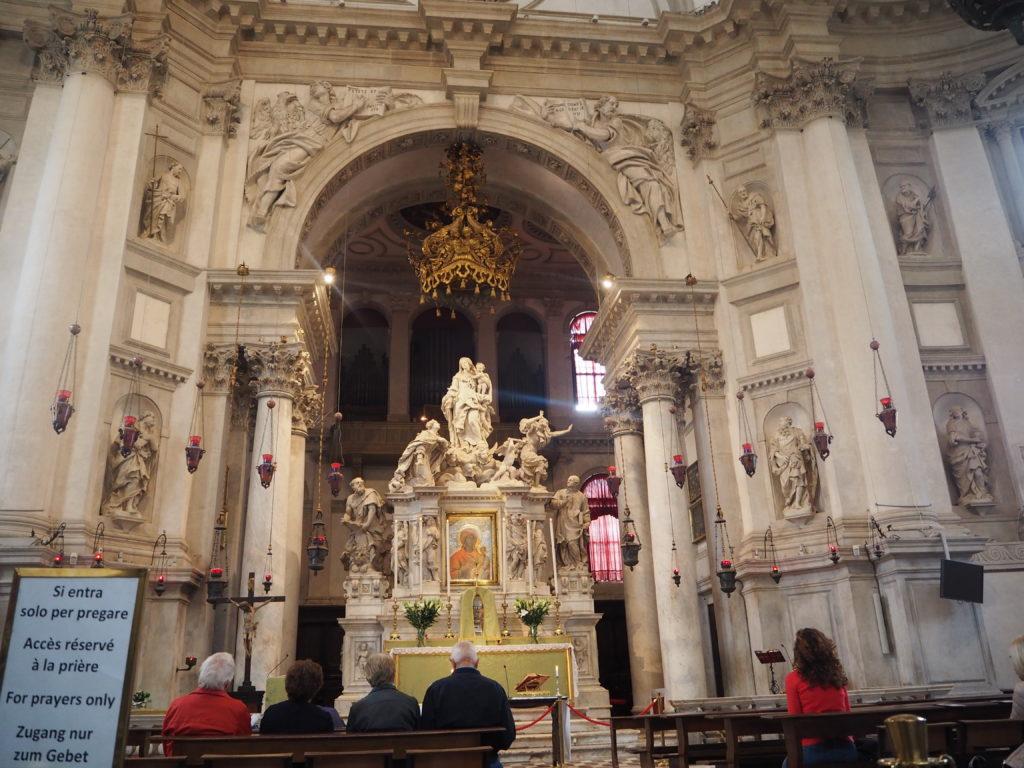 サンタ・マリア・デッラ・サルーテ教会(Basilica di Santa Maria della Salute)内部の中央祭壇で祈りを捧げる人々