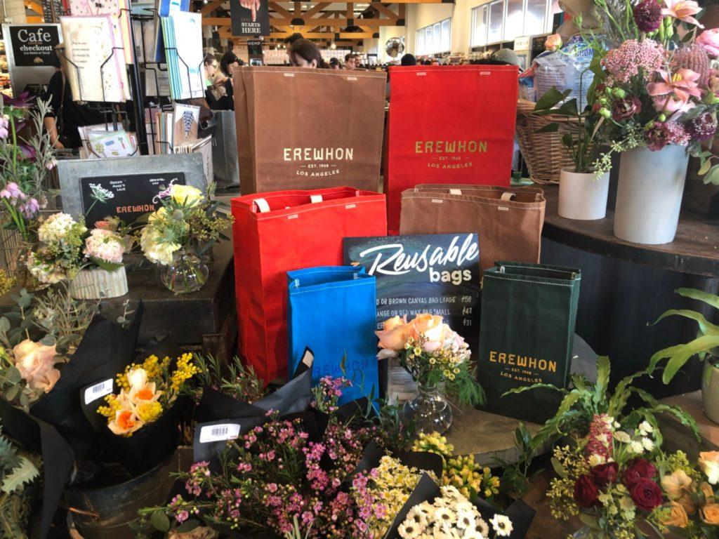 LAの超高級スーパー、エレウォン(Erewhon Market)店内入口のエコバッグと花